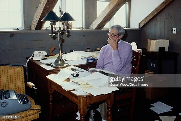 In the paper-strewn writing studio at his summer home, American writer and journalist George Plimpton sits at his desk, Wainscott, New York, January...