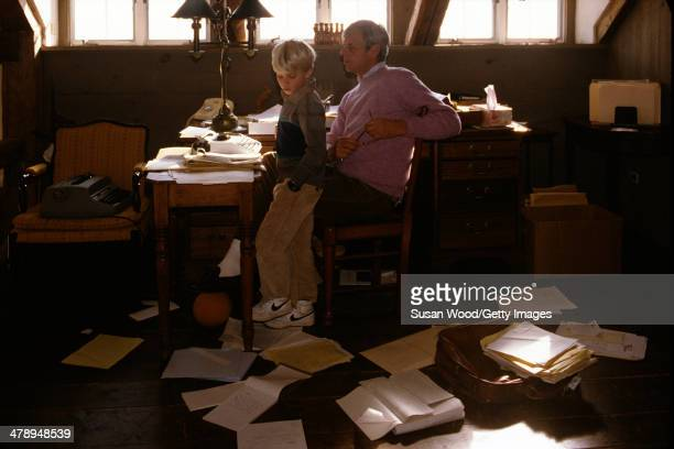 In the paper-strewn writing studio at his summer home, American writer and journalist George Plimpton sits at his desk with his son, Taylor Ames...