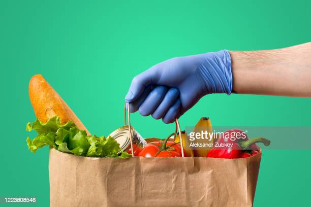 in the person's hand is a paper bag with food. donation and home delivery. - charitable donation stock pictures, royalty-free photos & images