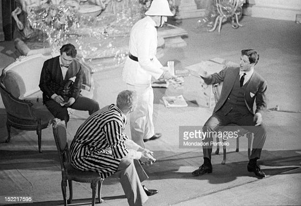 In the play 'Un marziano a Roma' Vittorio Gassman interprets the role of the Martian Kunt he is sat down with a black and white striped dressing gown...