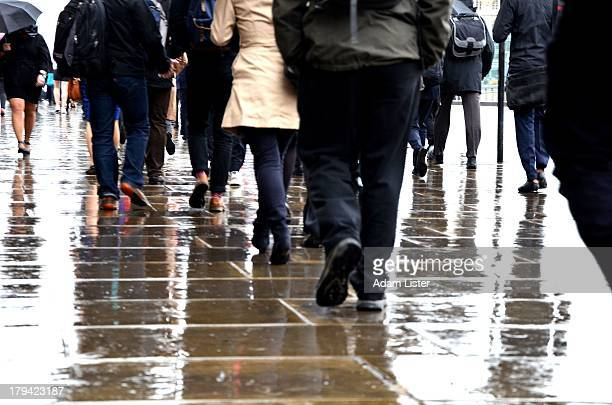 CONTENT] In the pouring heavy rain Londons Businessmen bankers financiers and City office workers are seen commuting during the daily rush hour They...
