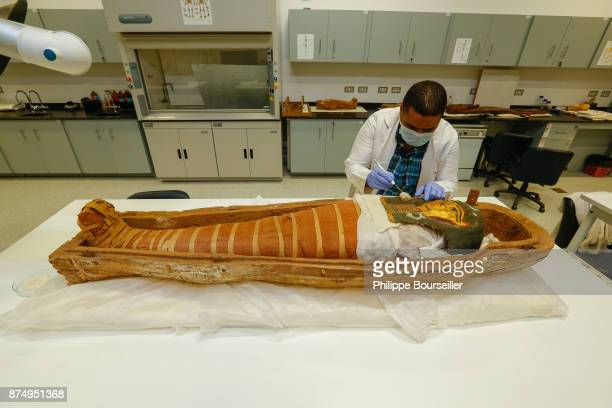 In the restoration laboratory of the GEM's mummies in Cairo curator Khaled Abdel Rady is dusting the mask of an ancient mummy from Fayoum