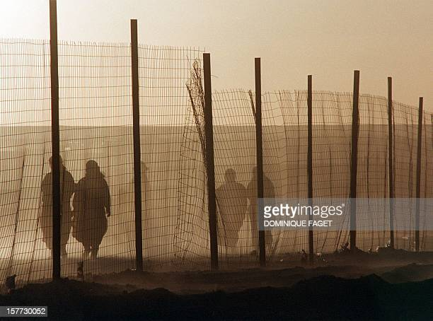 In the sand wind a group of Sahrawis refugee women walk behind the fence of Smara's camp 30 November in Tindouf Algeria A ceasefire in the conflict...