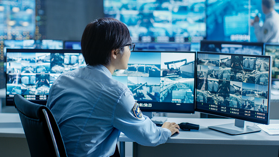 In the Security Control Room Officer Monitors Multiple Screens for Suspicious Activities. He's Surrounded by Monitors and Guards Facility of National Importance. 890157172