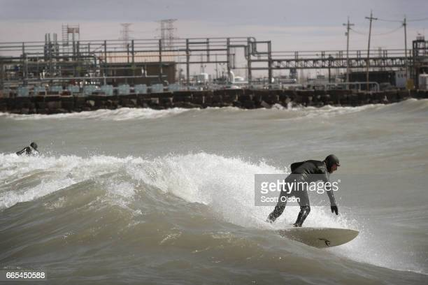 In the shadow of a refinery surfers surf the waves of Lake Michigan on April 6 2017 in Whiting Indiana The waves were pushed ashore by sustained...