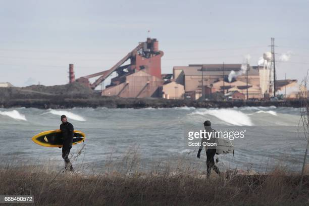 In the shadow of a steel mill surfers surf the waves of Lake Michigan on April 6 2017 in Whiting Indiana The waves were pushed ashore by sustained...
