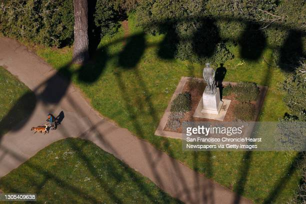 In the shadow of SkyStar Wheel, a man on roller skates is pulled by his dog past the statue of John J. Pershing as the 150-ft. High attraction...