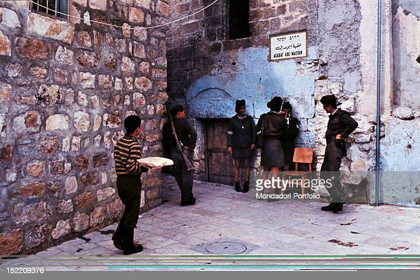 In the shadow of the AlAqsa Mosque and the Dome of the Rock armed Israeli militia chat among themselves during the patrol of the entrance of the...