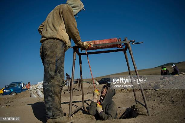 """In the Sharyngol district of Mongolia, a 16 year-old """"ninja"""" is lowered into a small hole about 10 feet deep where he will crawl around the..."""
