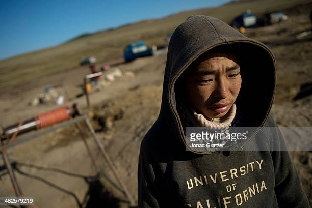 """In the Sharyngol district of Mongolia, a teenager """"ninja"""" works with the soil that was dug up from a 10 feet deep hole where the workers crawl in..."""