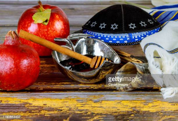in the synagogue are the symbols of rosh hashanah apples and honey - jewish prayer shawl stock pictures, royalty-free photos & images