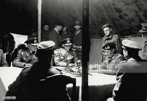 In the tent of his headquarter Marshal Bernard Law Montgomery on the right is reading the terms of surrender of the armed forces in Germany Denmark...