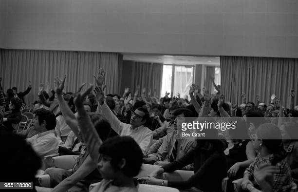 In the Time Life Building auditorium audience members raise their hands during an employeeorganized meeting to support the Moratorium to End the War...