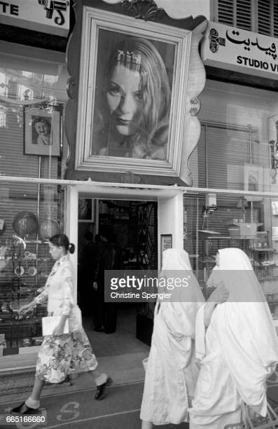 In the town center of Algiers two veiled women pass in front of a portrait of French actress Madeleine Sologne