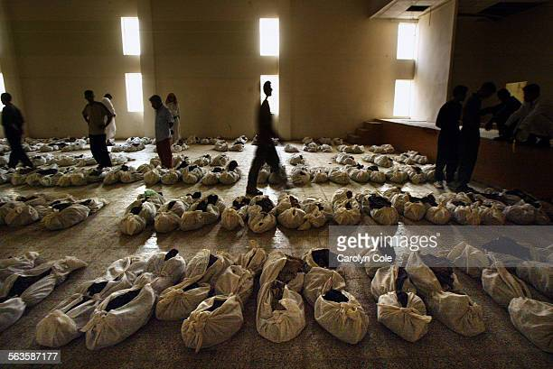 In the town of Mussaib, 372 bodies recovered from a mass grave were brought to the Islamic Youth Center, where family members look for their missing...