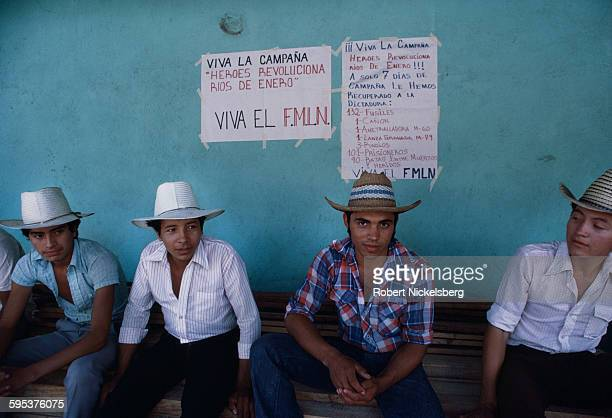 In the town square of a village held by Popular Revolutionary Forces guerrillas, a group of residents sit below hand-written rebel notices, Corinto,...