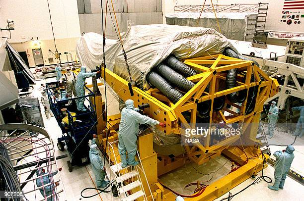 In the Vertical Processing Facility , workers check fittings and cables on the stand that will raise the Chandra X-ray Observatory to a vertical...
