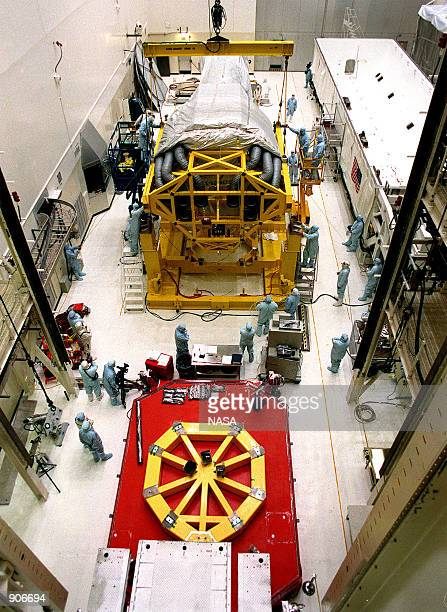 In the Vertical Processing Facility , workers check the placement of the Chandra X-ray Observatory on the stand on the floor. The stand will be used...