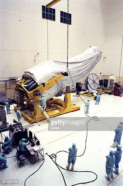 In The Vertical Processing Facility Workers Watch As The Overhead Crane Starts Lifting The Shrouded Chandra XRay Observatory To A Vertical Position...