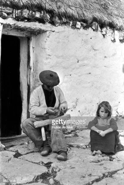In the village of Snichmaan on one of the three Aran Islands in Galway Bay a man sits outside a cottage making a pair of shoes out of cowhide The...