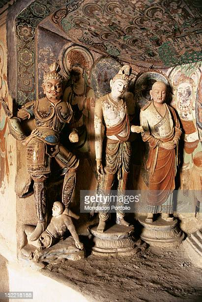 In the wall of a Buddhist temple, dug inside Mogao cave number 45, there is a niche containing three statues made of painted stucco, belonging to...