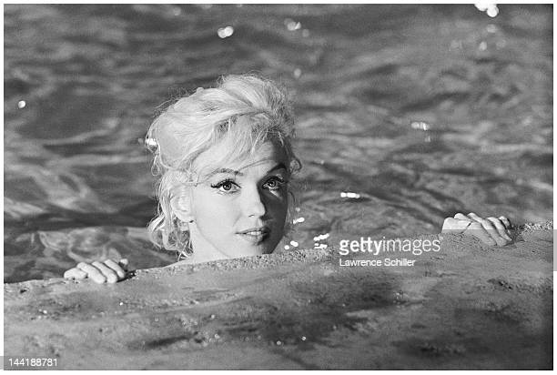 APPLY In the water American actress Marilyn Monroe looks over the edge of a pool for a scene during the filming of 'Something's Got to Give' Los...