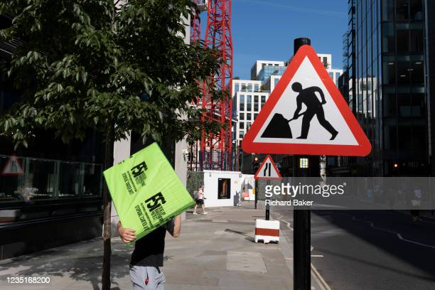 In the week that many more Londoners returned to their office workplaces after the Covid pandemic, a construction worker carries materials next to a...
