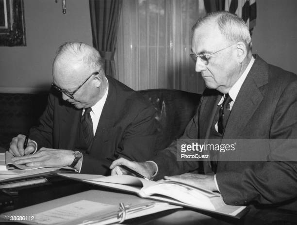 In the White House American politician US President Dwight D Eisenhower signs the Paris Agreements as US Secretary of State John Foster Dulles waits...
