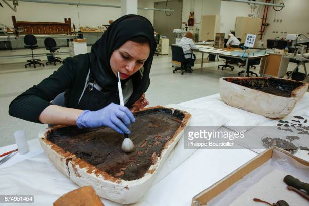 In the wood preservation laboratory the conservator Amira El Baroudy cleans one of the food cans from Touthankamon's tomb