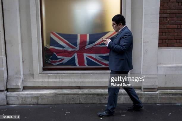 In the year that Britain will start the process of Brexit an Asian businessman walks past a crumpled British Union Jack flag in the window of a City...