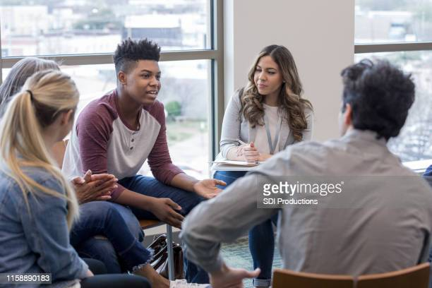 in therapy, teen boy shares life experiences with group - person in education stock pictures, royalty-free photos & images