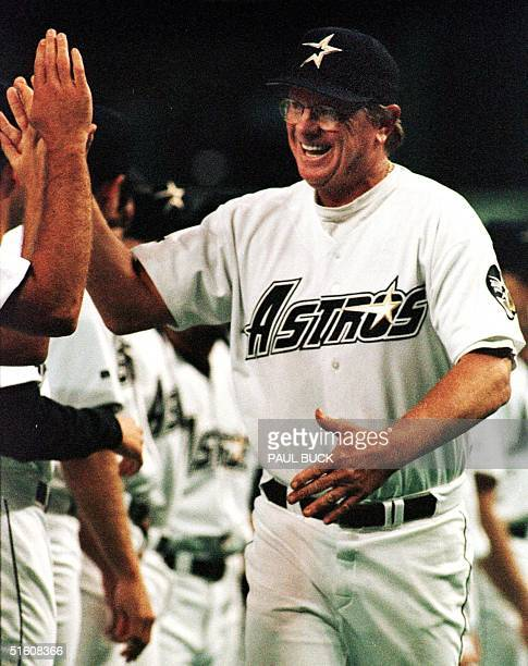 In this 06 April 1999 file photo Houston Astros manager Larry Dierker highfives teammates during player introductions on opening day at the AstroDome...