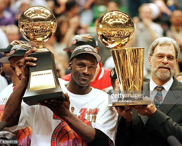 In this 14 June 1998 file photo, Michael Jordan holds the NBA Finals Most Valuable Player trophy and former Chicago Bulls head coach Phil Jackson...