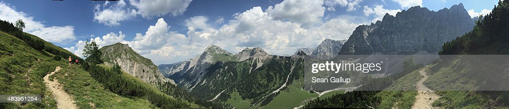 In this 180 degree panorama photo hikers, family members of the photographer, walk along a path near Falkenhuette hut in the Karwendel mountain range on August 8, 2015 near Herrenhaeuser, Austria. The Karwendel mountain range, part of the Austrian Alps, is located in central Tyrol and is a popular summer destination for mountain bikers, climbers and hikers. Mountain huts operated by alpine clubs and scattered across the region offer food and shelter.