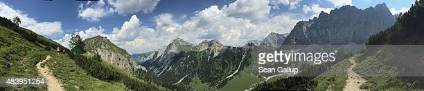 In this 180 degree panorama photo hikers family members of the photographer walk along a path near Falkenhuette hut in the Karwendel mountain range...