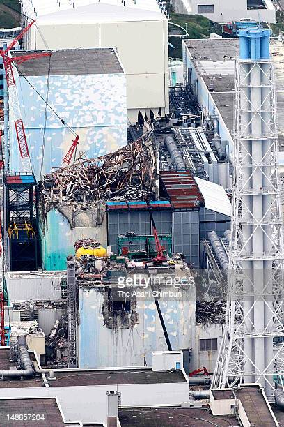 In this aerial image a crane left swings into action to remove nuclear fuel from the No 4 reactor building at the Tokyo Electric Power Co Fukushima...