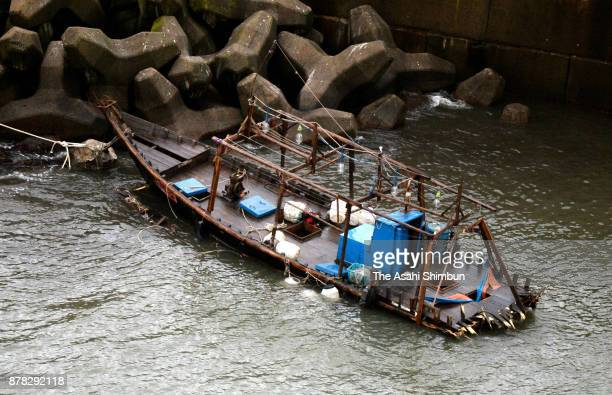 In this aerial image a damaged wooden boat is seen at a marina on November 24 2017 in Yurihonjo Akita Japan Eight men found in the boat said they...