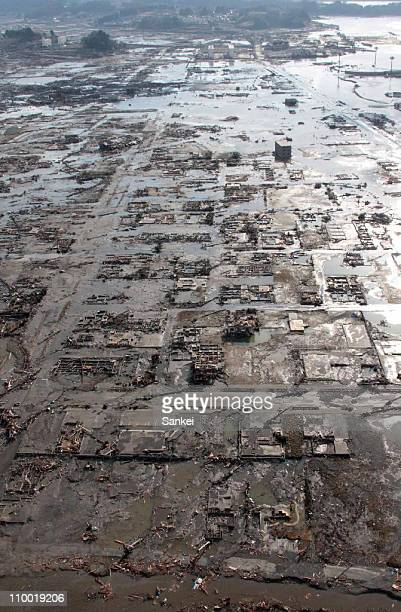In this aerial image, a general view of Rikuzentakata City as a tsunami washes away buildings on March 12, 2011 in Rikuzentakata, Iwate, Japan. An...