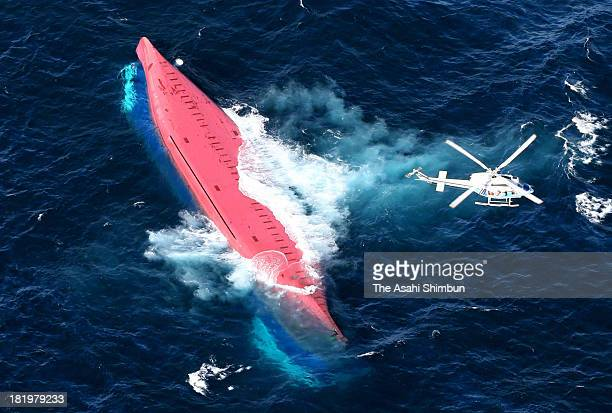In this aerial image a Japan Coast Guard helicopter flies above the capsized freighter Dai 18 Eifuku Maru 11kilometre off the Izu Oshima island on...