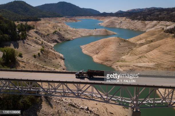 In this aerial image, a logging truck drives across the Enterprise Bridge as dry land is exposed on the banks of Lake Oroville reservoir due to low...