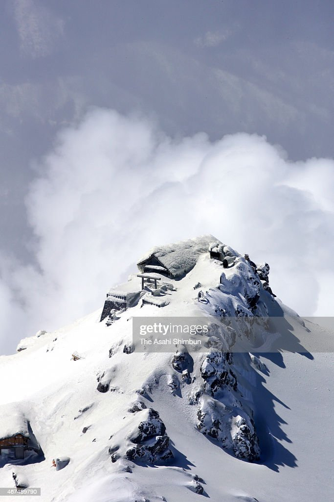 In this aerial image, a shrine gate and structure atop the volcano was covered with snow on the summit of Mount Ontake while volcanic plumes rise on March 25, 2015 in Otaki, Nagano, Japan. Fifty-seven trekkers were killed and six were unaccounted for in the September 27 eruption of the 3,067-meter-high mountain, which straddles Nagano and Gifu prefectures in central Japan.