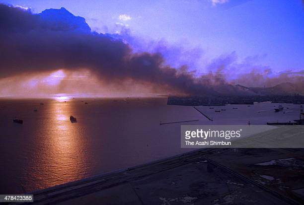 In this aerial image black smoke from Kobe city covers Kobe bay after the strong earthquake on January 17 1995 in Kobe Hyogo Japan Magnitude 73...