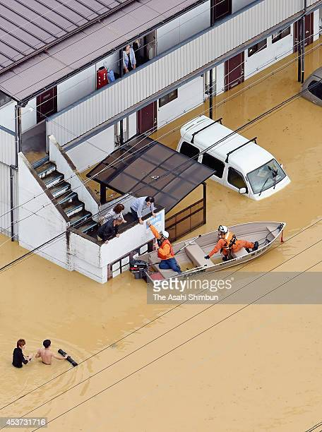 In this aerial image fire fighters in rescue operation at a flooded apartment on August 17 2014 in Fukuchiyama Kyoto Japan Fukuchiyama City recorded...