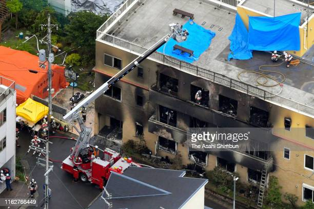 In this aerial image, fire fighters investigate the fire site after an arson at a studio of Kyoto Animation Co. On July 18, 2019 in Kyoto, Japan....