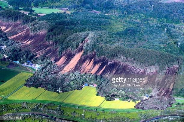 In this aerial image, houses are buried by multiple landslides after a powerful earthquake jolt on September 6, 2018 in Atsuma, Hokkaido, Japan. The...