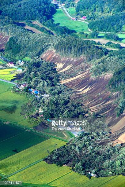In this aerial image, houses are buried by multiple landslides after a powerful earthquake jolted at Yoshino district on September 6, 2018 in Atsuma,...