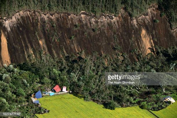 In this aerial image, houses are buried by multiple landslides after a powerful earthquake at Yoshino district on September 6, 2018 in Atsuma,...