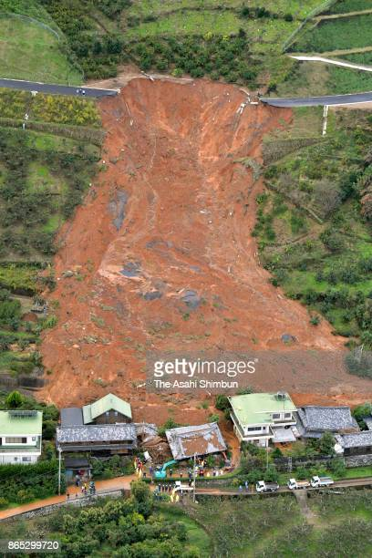 In this aerial image, houses engulfed by a landslide is seen after powerful Typhoon Lan hit past on October 23, 2017 in Kinowaka, Wakayama, Japan. A...