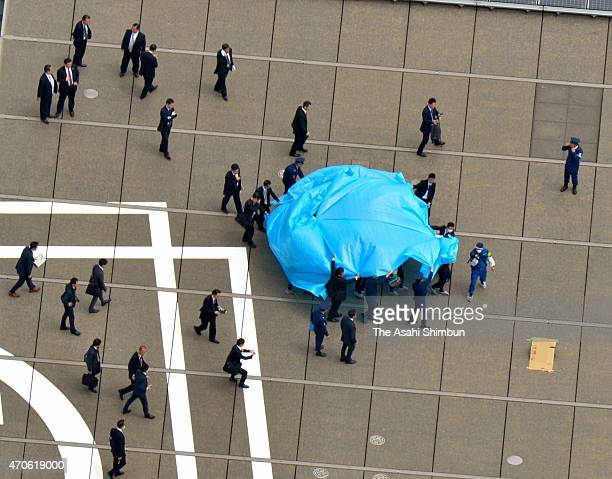 In this aerial image investigators approach to a drone under tarpaulin on the roof of the prime minister's official residence on April 22 2015 in...