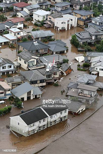 In this aerial image Japan Ground SelfDefense Force helicopter rescue residents as they are isolated by the flooding of the Shirakawa River on July...